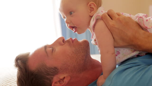 side view of father on bed with baby daughter. - genderblend stock videos & royalty-free footage