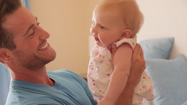vidéos et rushes de side view of father on bed with baby daughter. - 2 5 mois