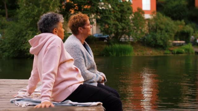 side view of female friends talking on pier by lake - dreiviertelansicht stock-videos und b-roll-filmmaterial