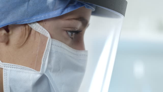 vídeos de stock e filmes b-roll de side view of female nurse working wearing face mask and shield - equipamento