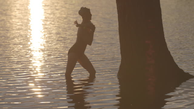 vídeos y material grabado en eventos de stock de side view of female swimmer doing stretching exercise by tree trunk in lake during sunset - gorro de baño