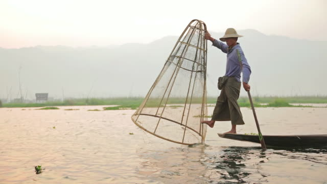 ws side pov view of fisherman on inle lake casting his net into water / inle lake, shan state, myanmar  - 漁師点の映像素材/bロール
