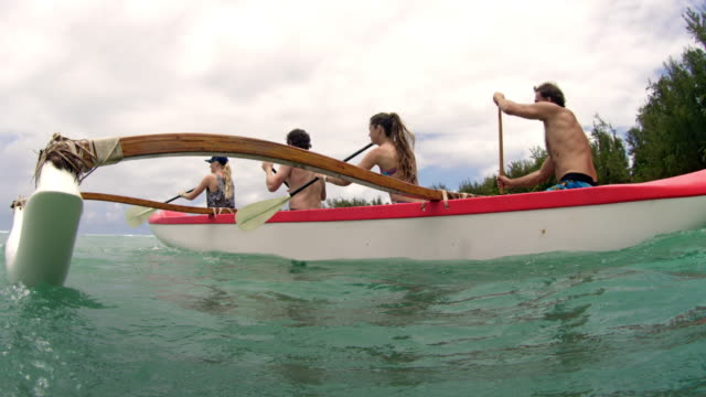 side view of four people in outrigger passing camera at water level - pagaiare video stock e b–roll