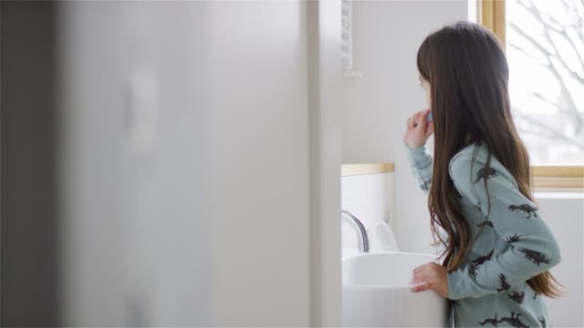 side view of girl brushing teeth in bathroom - brushing stock videos & royalty-free footage