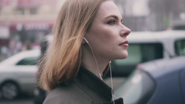 Side view of girl in headphones walking on the street