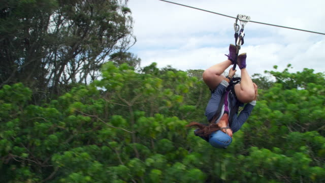 side view of girl ziplining through canopy upside down - generation z stock videos & royalty-free footage