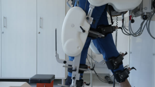 side view of handsome man walking on treadmill with the help of a exoskeleton robot during therapy - physiotherapy stock videos & royalty-free footage