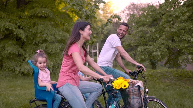 side view of happy family enjoying bike ride together. - side view stock videos & royalty-free footage
