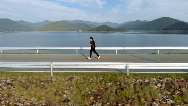 side view of man jogging in the morning on lake and mountain view - carrellata video stock e b–roll