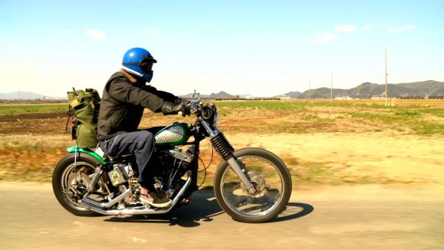 スローモーションで田舎道をバイクに乗る男の側面図 - バイカー点の映像素材/bロール