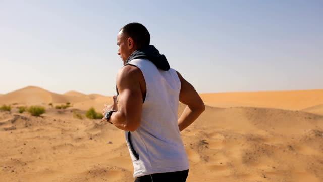 Vista lateral do homem correndo no deserto
