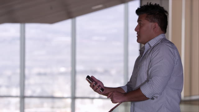 Side view of man talking on a smartphone.