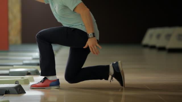 vídeos de stock, filmes e b-roll de side view of man throwing duckpin bowling ball - sapato de boliche