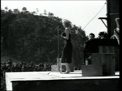 side view of marilyn monroe performing on stage for troops in korea / she waves to crowd. marilyn monroe performing for troops in korea on february... - 1954 stock-videos und b-roll-filmmaterial
