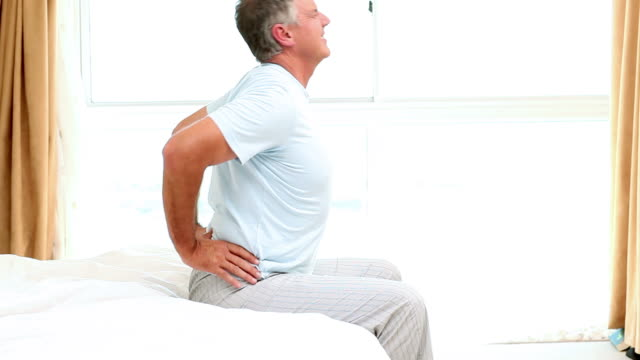 Side view of man experiencing back pain on the edge of his bed