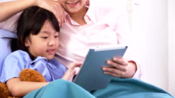 side view of mid section: Mother is belong to Japanese girl with a digital tablet in the hospital ward