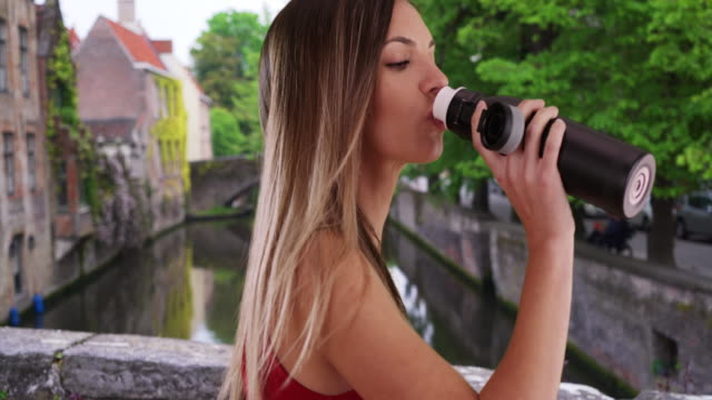 side view of millennial woman drinking water from bottle in bruges, belgium - bottiglia video stock e b–roll