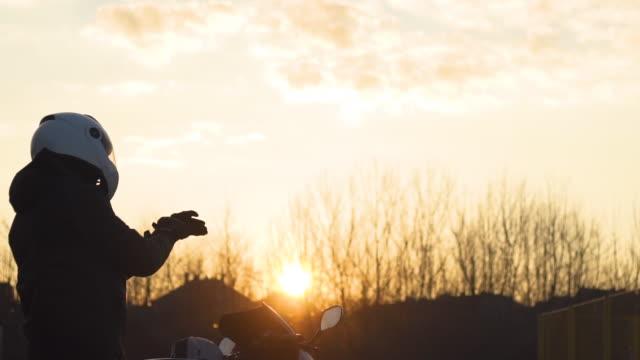 vídeos de stock e filmes b-roll de side view of motorcyclist taking gloves - corrida