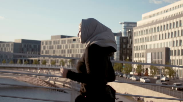 side view of muslim woman in hijab running in the berlin center - hijab stock videos and b-roll footage