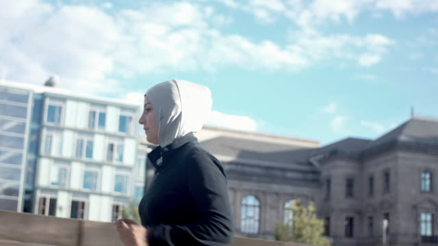 side view of muslim woman in sport hijab running in the city - hijab stock videos and b-roll footage
