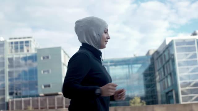 vidéos et rushes de vue latérale d'une femme musulmane en hijab de sport en cours d'exécution dans la ville - joggeuse