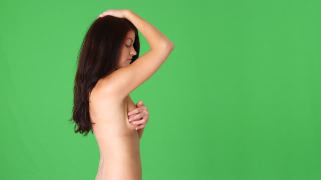 side view of naked woman giving herself a breast exam - 人体部位点の映像素材/bロール