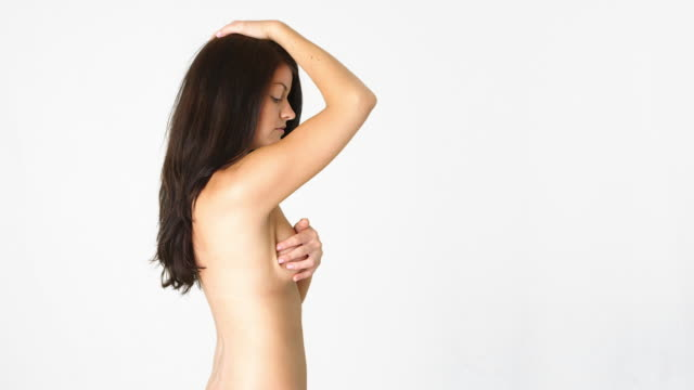 stockvideo's en b-roll-footage met side view of naked woman giving herself a breast exam - 20 24 jaar