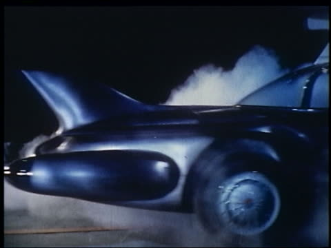 vídeos de stock e filmes b-roll de 1956 side view of rear end of black futuristic car driving in smoke - 1956