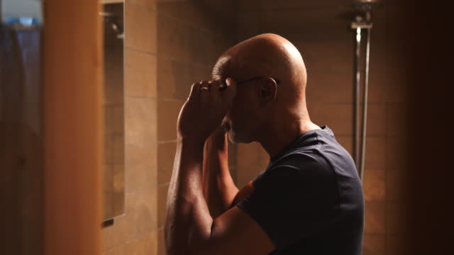 vídeos de stock e filmes b-roll de side view of retired senior male looking at mirror while wearing eyeglasses in bathroom - careca