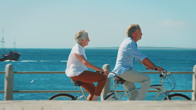 Side view of senior couple riding tandem bicycle