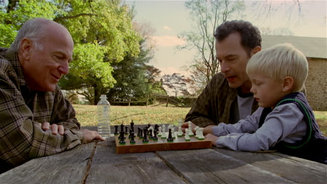 side view of senior man playing chess against mature man and young boy outdoors / autumn - grandfather stock videos & royalty-free footage