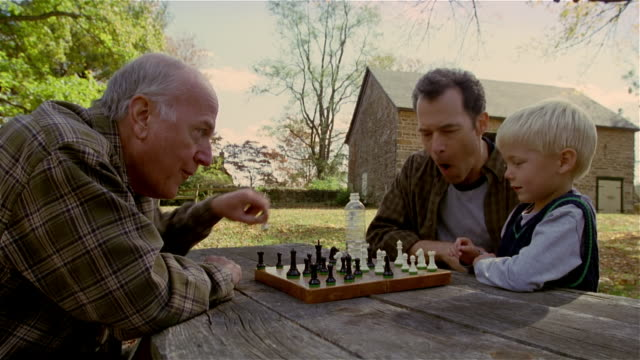 side view of senior man playing chess against mature man and young boy outdoors / mature man feigning shock/ men congratulating boy on good move / autumn - großvater stock-videos und b-roll-filmmaterial