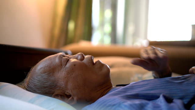 side view of sick senior man on bed at home - sad old asian man stock videos & royalty-free footage