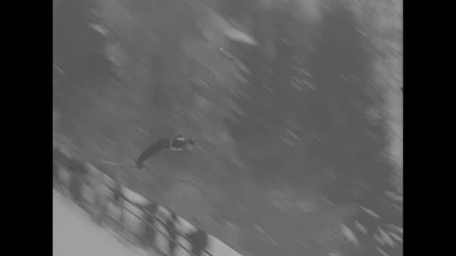 ms side view of ski jumper taking off / ms follow ski jumper taking off landing falling / mcu people watching / vs jumper starts down run takes off... - garmisch partenkirchen stock videos & royalty-free footage