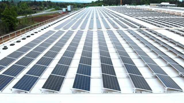 side view of solar panels lined up on the roof of a factory - solar powered station stock videos & royalty-free footage