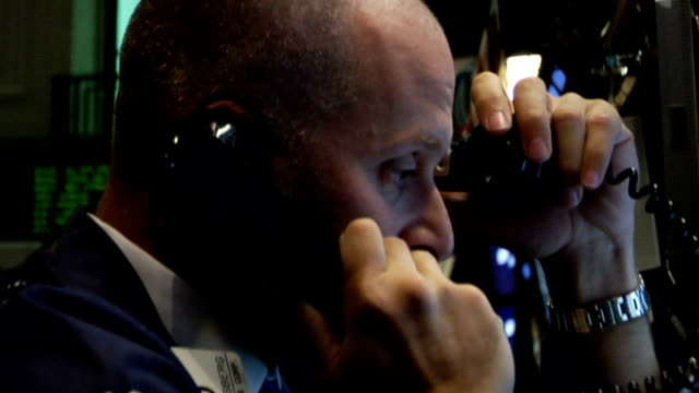 side view of trader on two phones at workstation on trading floor of new york stock exchange new york city - 2008 stock videos and b-roll footage