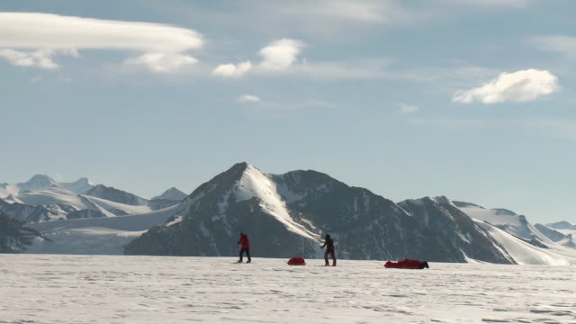 ws side view of two people on skis pulling sleds across snowy landscape with mountains / union glacier, heritage range, ellsworth mountains, antarctica - exploration stock videos & royalty-free footage