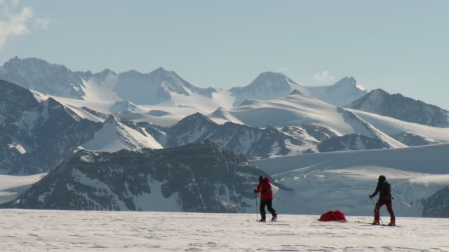 ws side view of two people on skis pulling sleds across snowy landscape with mountains / union glacier, heritage range, ellsworth mountains, antarctica - bastoncino da sci video stock e b–roll