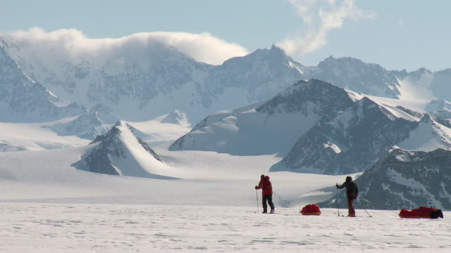 ws side view of two people on skis pulling sleds across snowy landscape with mountains / union glacier, heritage range, ellsworth mountains, antarctica - antarctica people stock videos & royalty-free footage