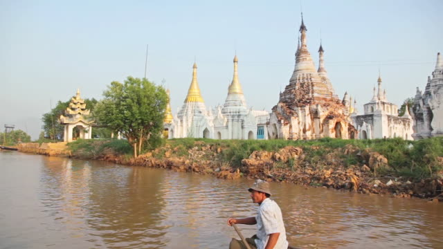 ws side pov view of white temples seen from inle lake (daytime), boat with three people on it passing by / inle lake, shan state, myanmar   - shan state stock videos & royalty-free footage