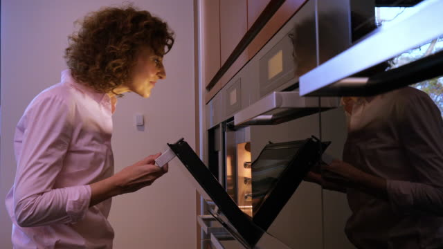 side view of woman checking food in the oven - oven stock videos & royalty-free footage
