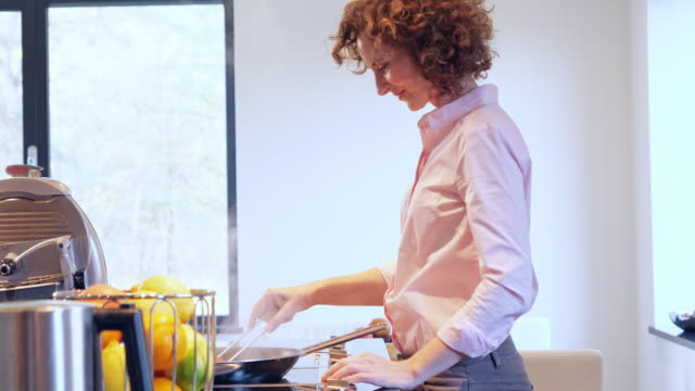 side view of woman cuooking in the kitchen - cooking pan video stock e b–roll