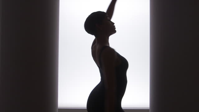 vídeos de stock e filmes b-roll de side view of woman dancing in front of bright light - body de ginástica