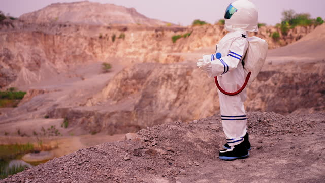 side view of woman in astronaut suit walking to see water lake and green plant while exploring mars in a desert area with feeling successful and happiness.  dreaming of human being to meeting water source, a new life. - astronaut stock videos & royalty-free footage