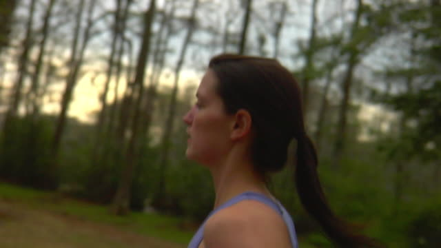 SLO MO CU TS SELECTIVE FOCUS Side view of woman jogging in forest, Wilmington, North Carolina, USA