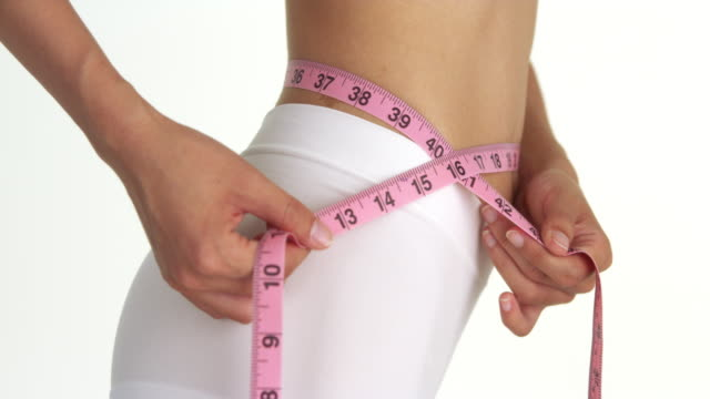 side view of woman measuring waist - waist stock videos & royalty-free footage