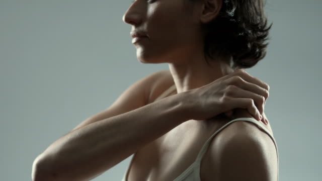 vídeos de stock, filmes e b-roll de slo mo ms pan side view of woman rubbing her back and in studio / new york city, new york state, usa - ombro