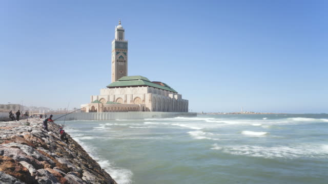 vídeos de stock, filmes e b-roll de ws t/l  side view of world's third largest mosque of hassan ii and mens doing fishing near sea shore / casablanca, morocco - mesquita