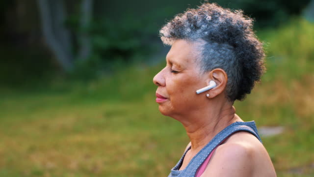 side view of wrinkled woman with in-ear headphones meditating in park - mindfulness stock videos & royalty-free footage