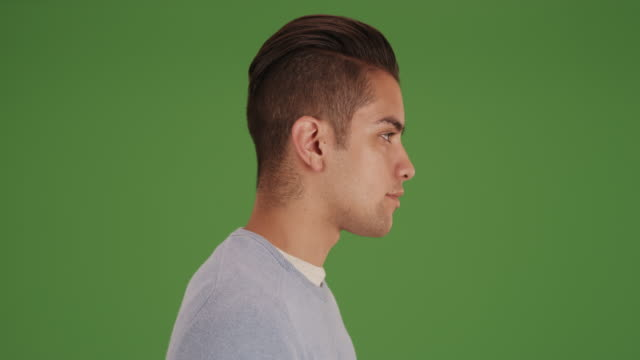 vídeos de stock e filmes b-roll de side view of young millennial man with undercut on green screen - perfil vista lateral